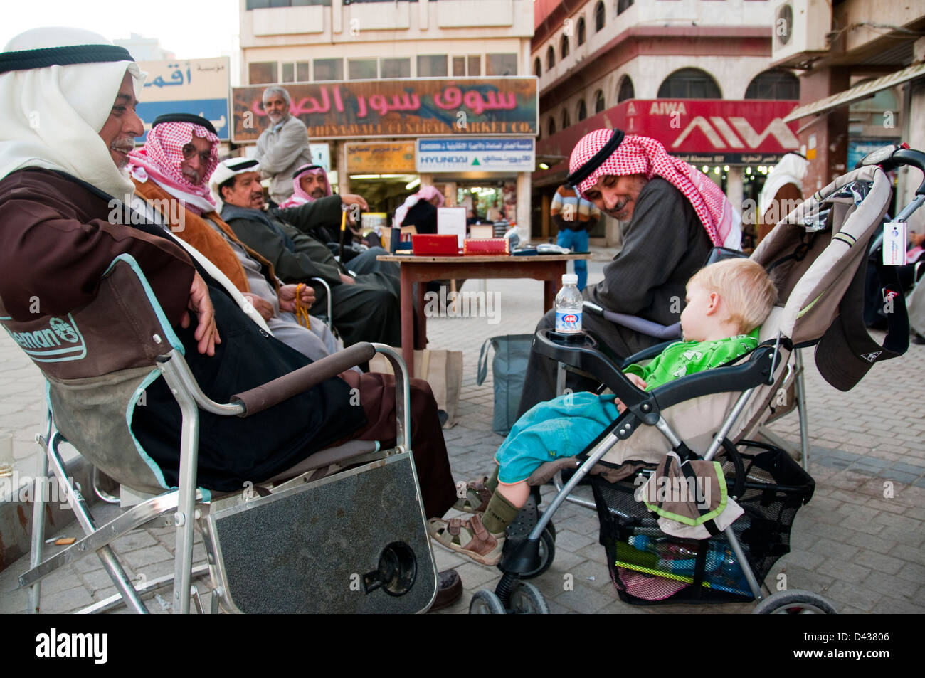 Young tourist boy asleep in stroller attracts many looks from friedly locals, Souk Al-Mubarak, Kuwait - Stock Image