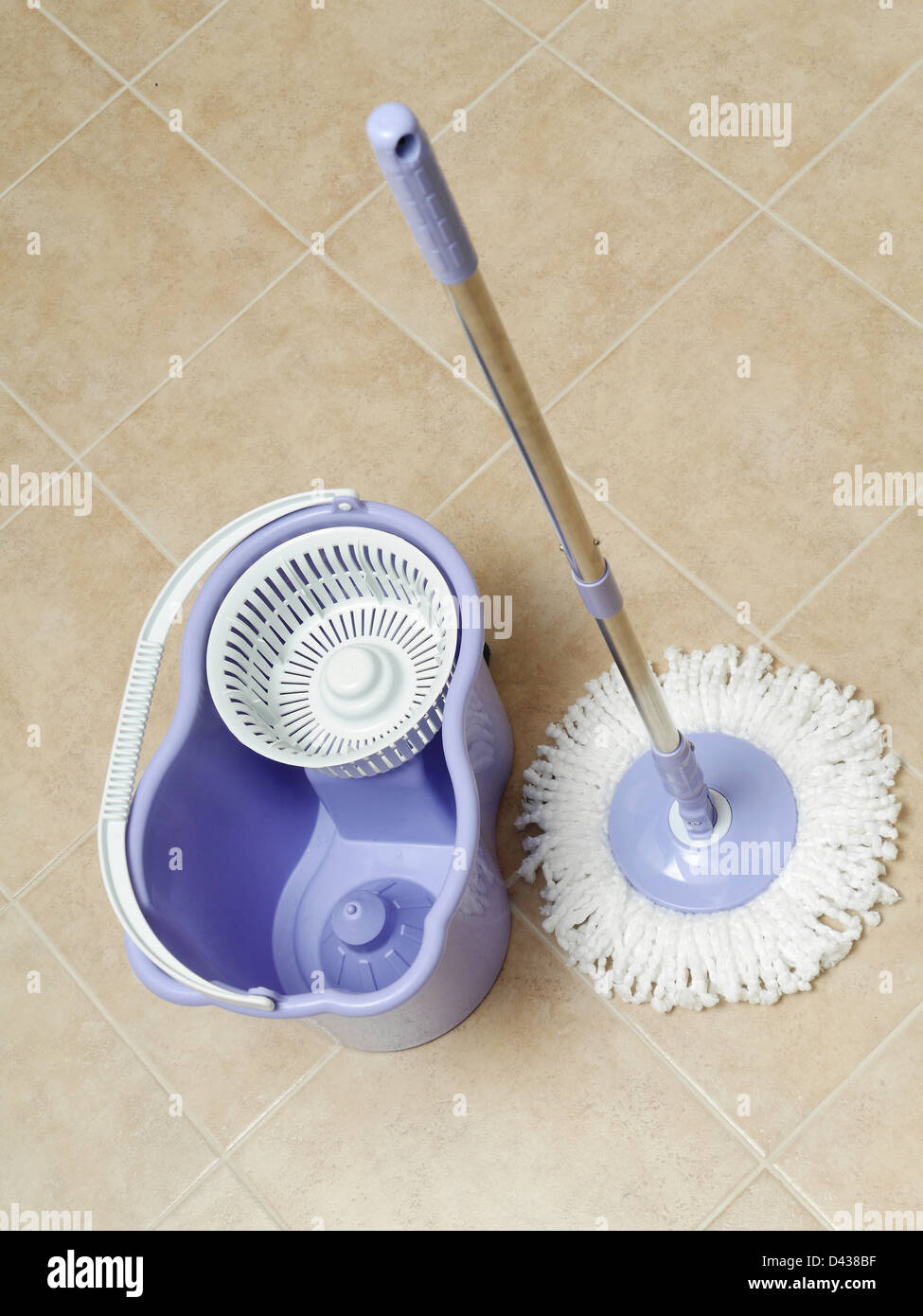 Rotary mop and empty bucket on tile floor - Stock Image