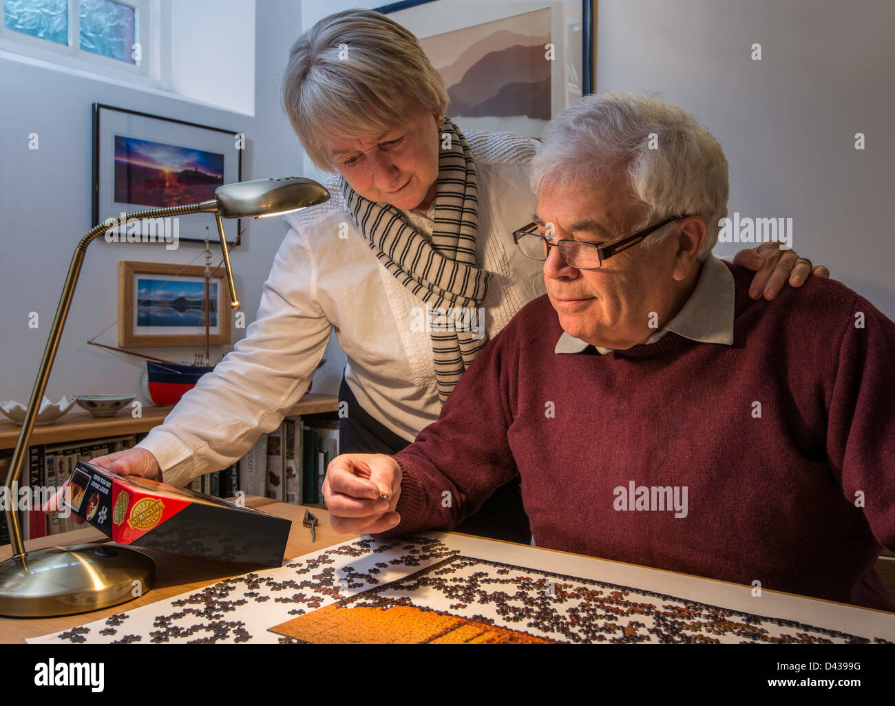 OAPs, RETIRED COUPLE, HUSBAND AND WIFE, WITH JIGSAW - Stock Image