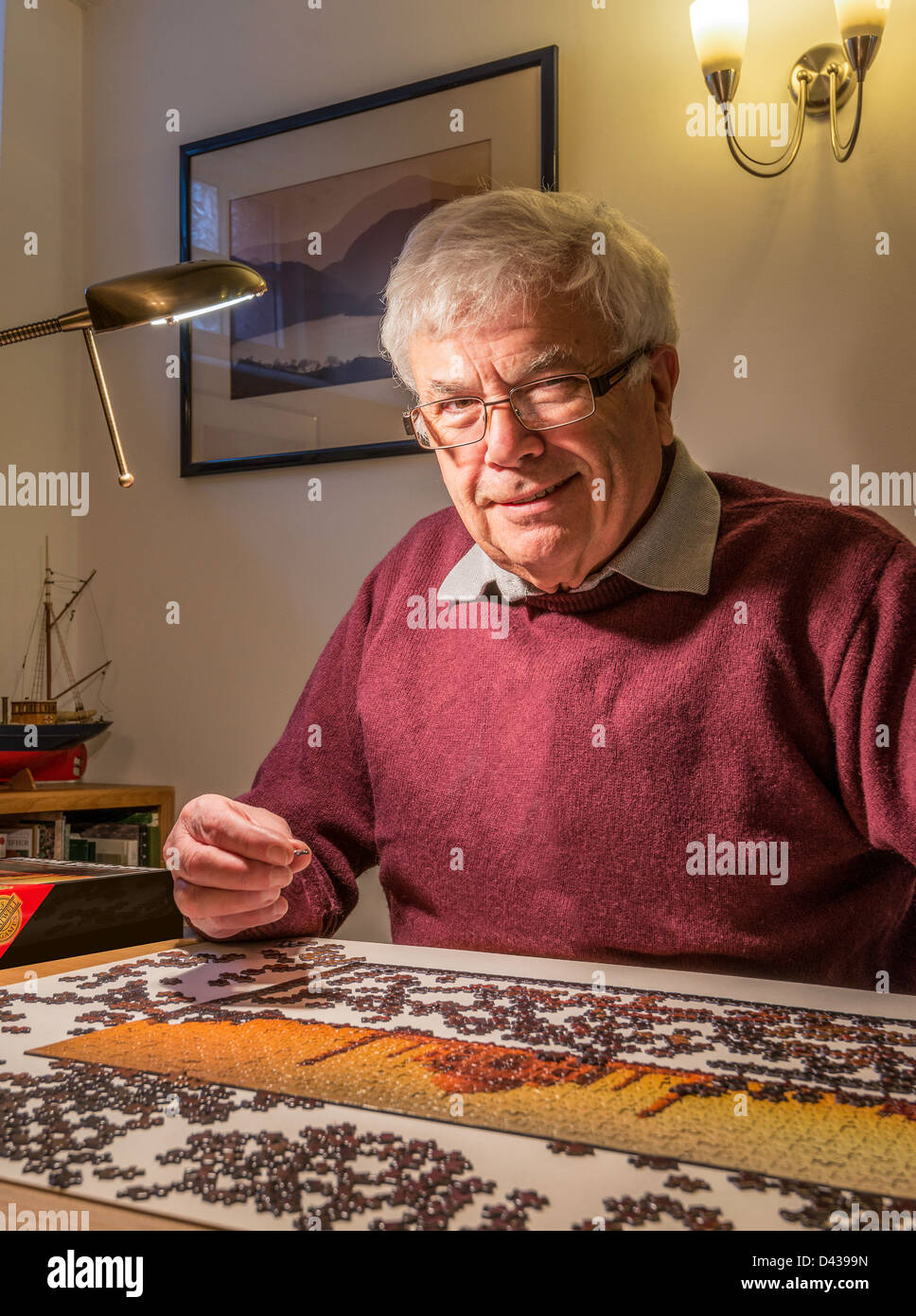 RETIRED MAN, OAP,  WITH JIGSAW LOOKING AT CAMERA - Stock Image