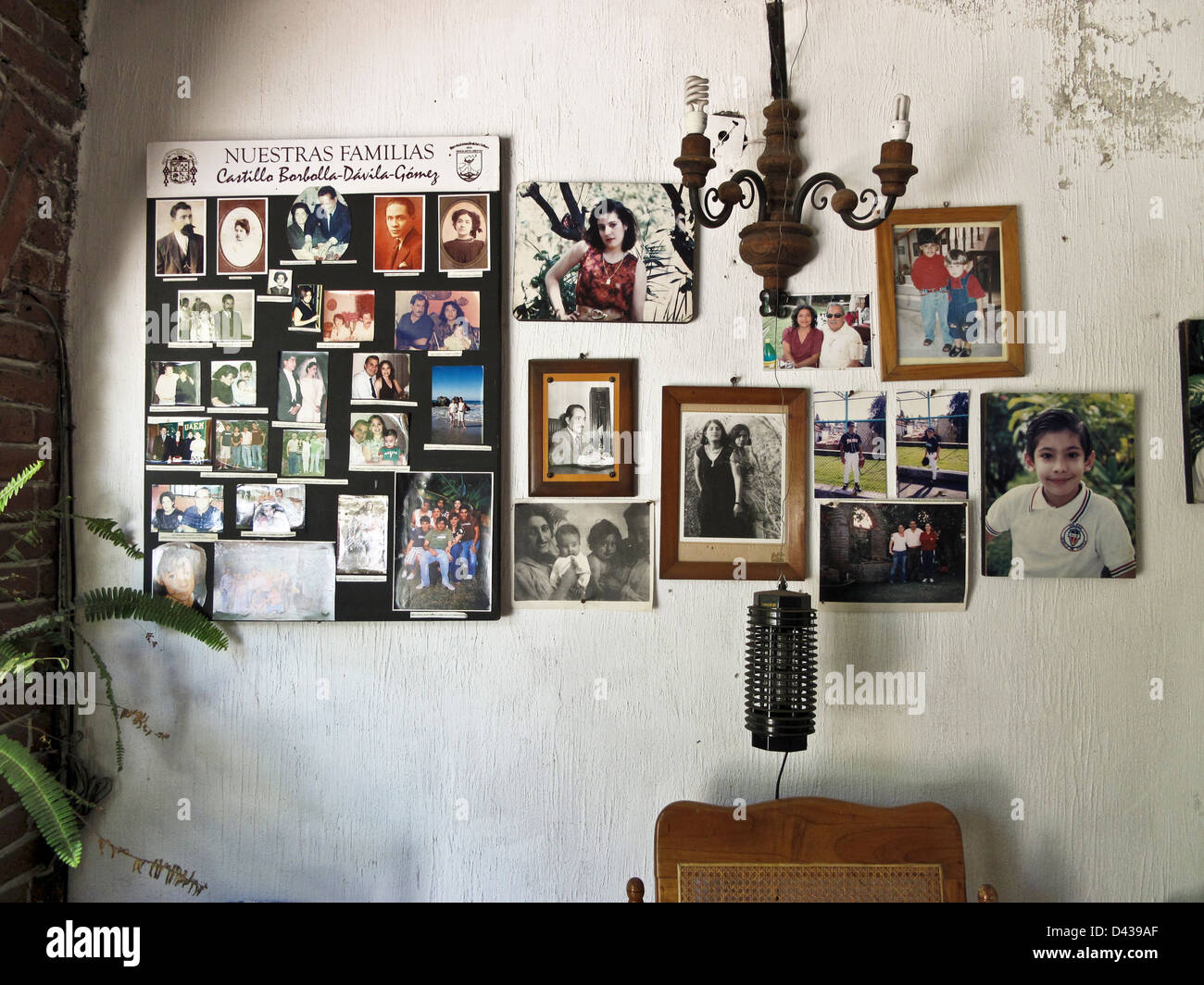 porch wall of Mexican middle class house home hung with 4 generations of family photo photos photographs Oaxaca - Stock Image