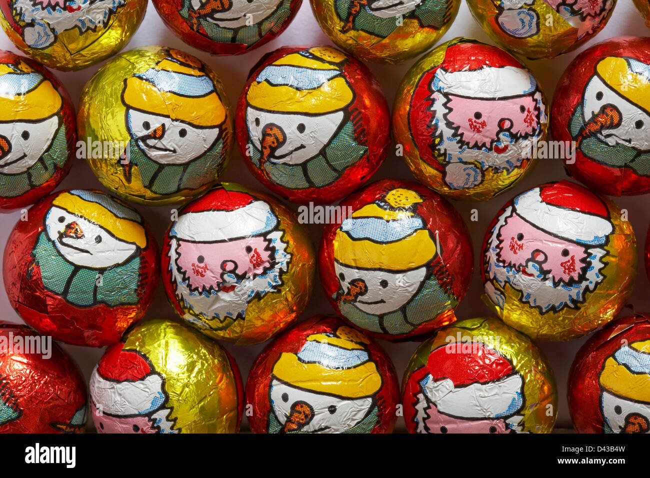 Christmas foil wrapped chocolate balls with snowmen and Father Christmas, Santa Claus, on chocolates ready for Christmas - Stock Image