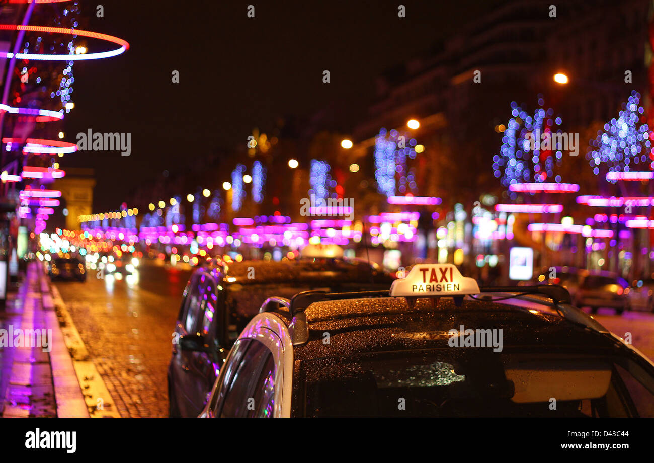 Taxi in Paris with the illuminated for Christmas Champs Elysées  and Arc de Triumph background - Stock Image