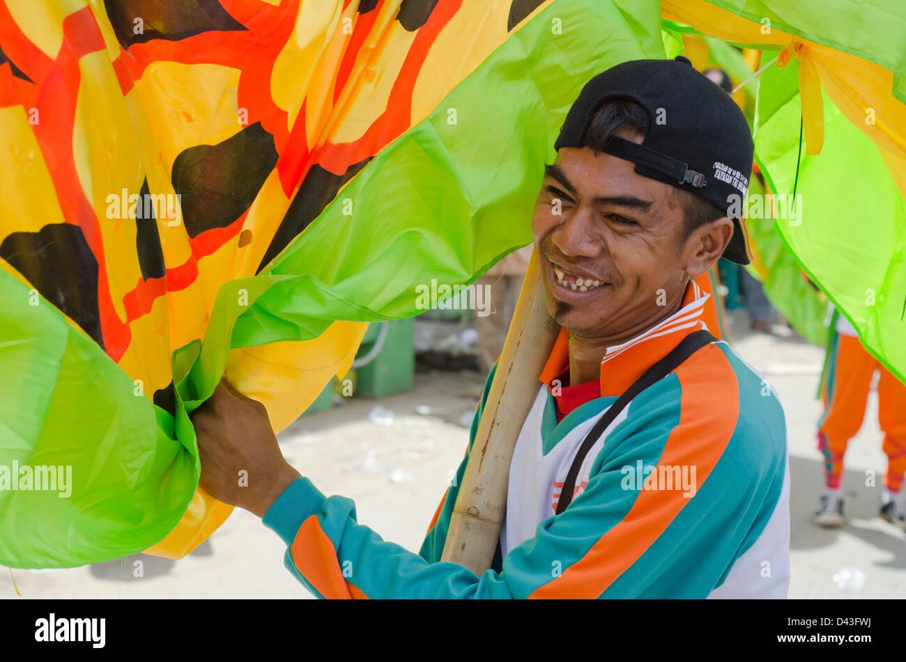Indonesian man holding up dragon in Chinese New Year parade, Ketapang, West Kalimantan, Indonesia. - Stock Image