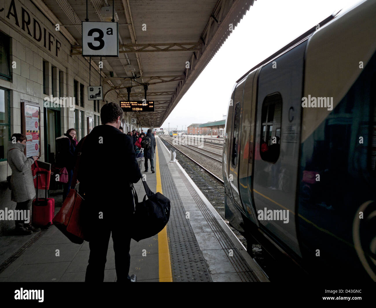 Arriva train approaching with passengers waiting on platform 3a at Cardiff train station South Wales UK - Stock Image