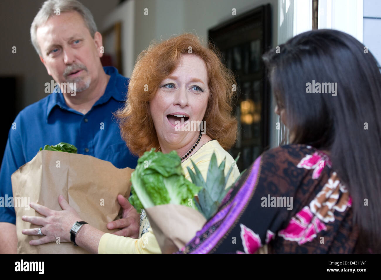 Look of surprise emotion is on the recipients faces as a charity relief worker brings bags of food and groceries - Stock Image