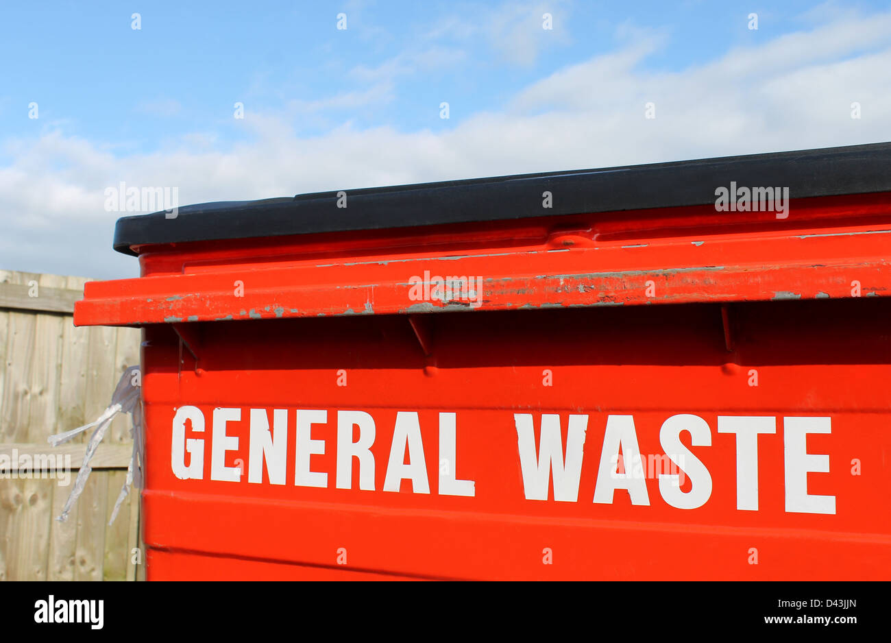 Industrial general waste bin with cloudscape background. - Stock Image
