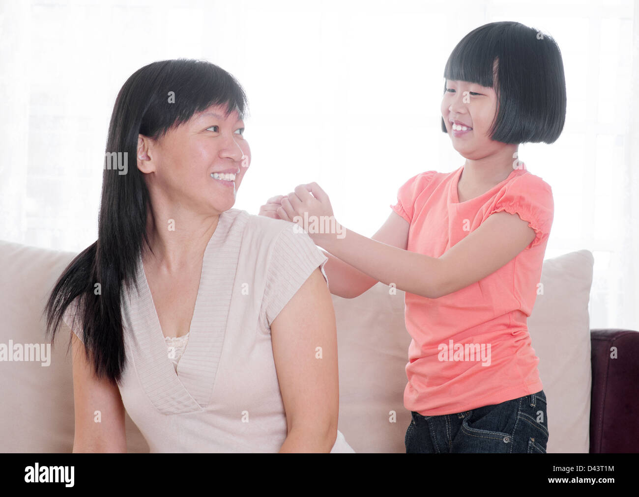 Filial piety concept. Southeast Asian child doing shoulder massage to her mother at home. Stock Photo