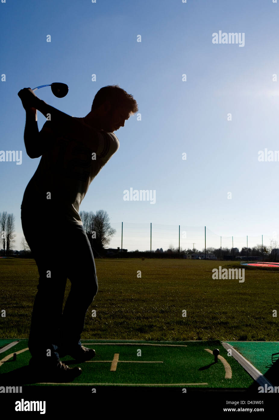 man silhouette at the driving range - Stock Image