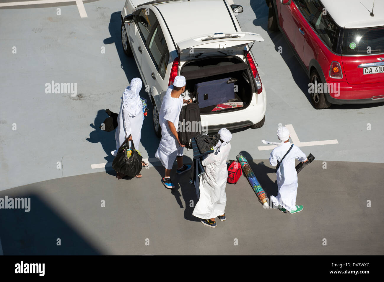 Muslim family wearing traditional white clothing packing the boot of a hire car - Stock Image