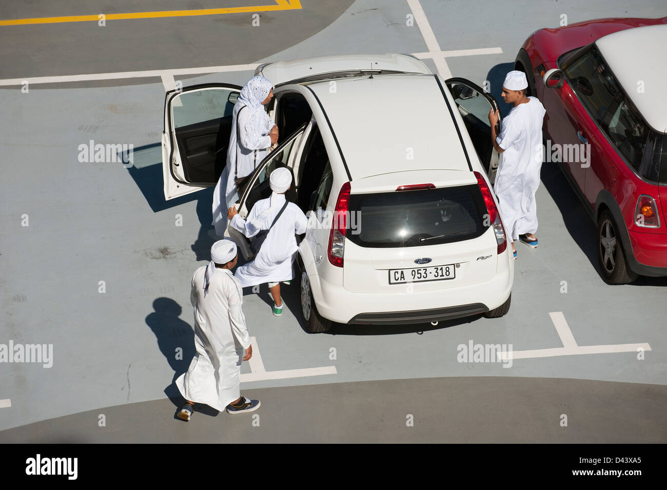 Muslim family in traditional white clothing get into a saloon car - Stock Image