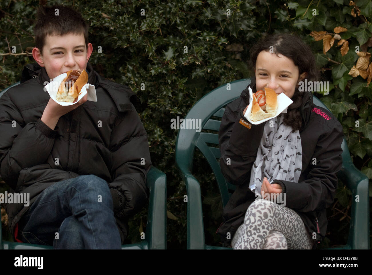 Two youngsters eating hot dogs at Farnham Farmers' Market, Farnham, Surrey, UK. - Stock Image