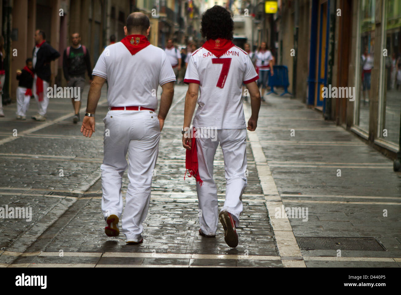 Young men walk along the streets of Pamplona wearing the traditional red and white clothes during San Fermin festival. Stock Photo