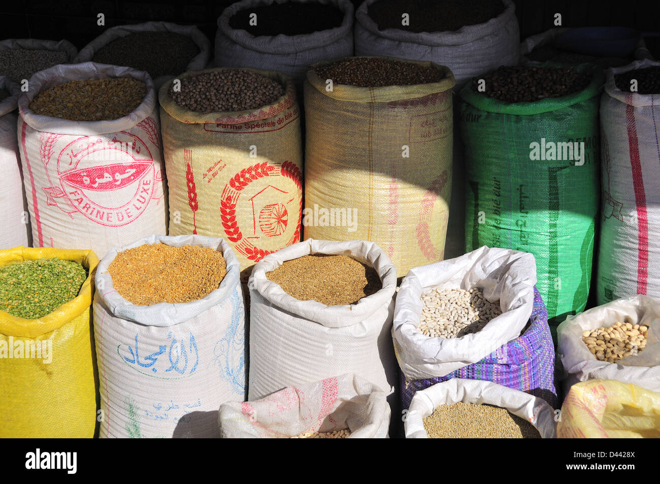 Sacks of colourful herbs and spices for sale in a market in Marrakesh, Morocco - Stock Image
