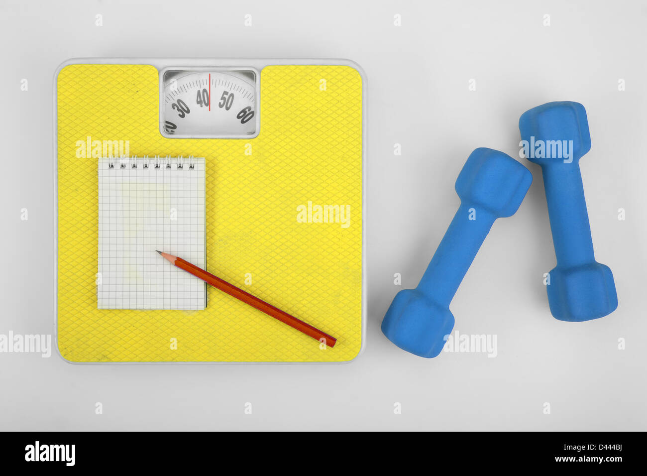 Scales, notebook with pencil and a dumbbell. - Stock Image
