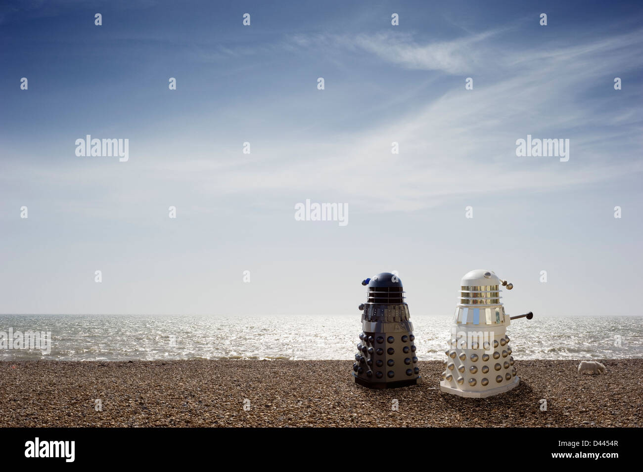 Two Dr Who Daleks taking their dog for a walk on the beach, UK - Stock Image