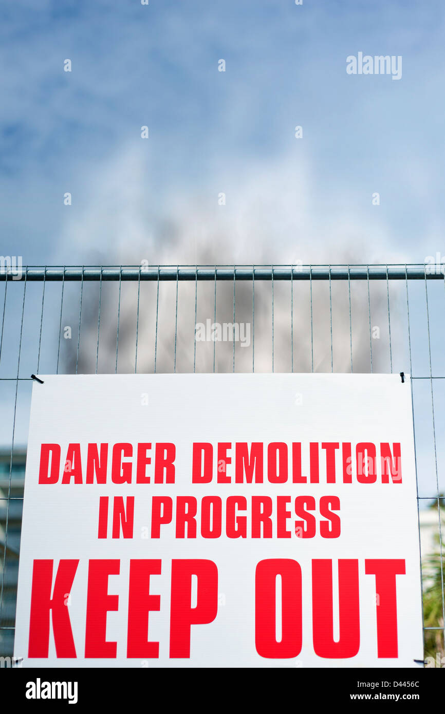 Sign reading ' Danger Demolition in Progress KEEP OUT ' with rising smoke behind it, UK - Stock Image