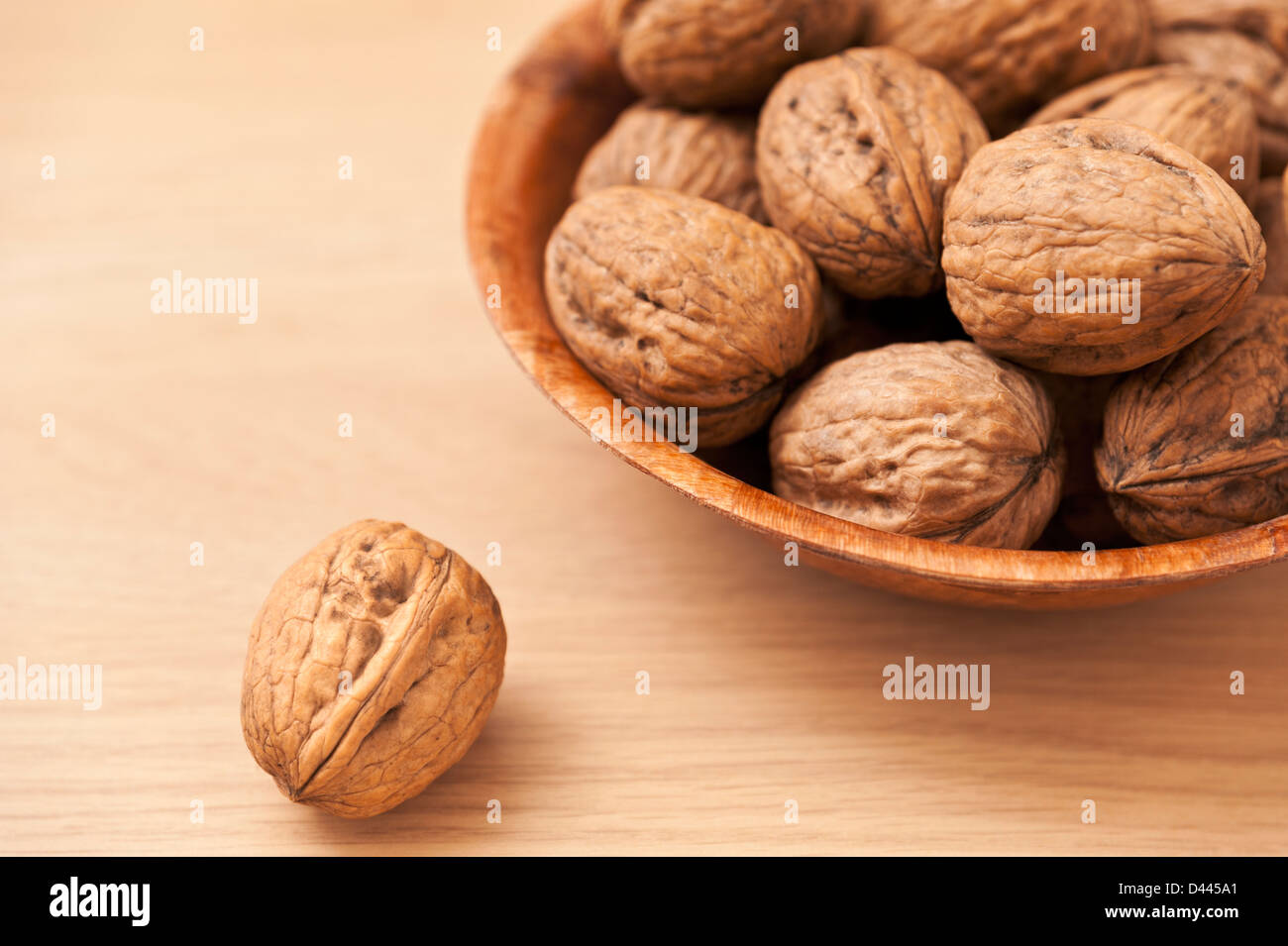 Bowl of Walnuts with one single Walnut in the foreground - Stock Image