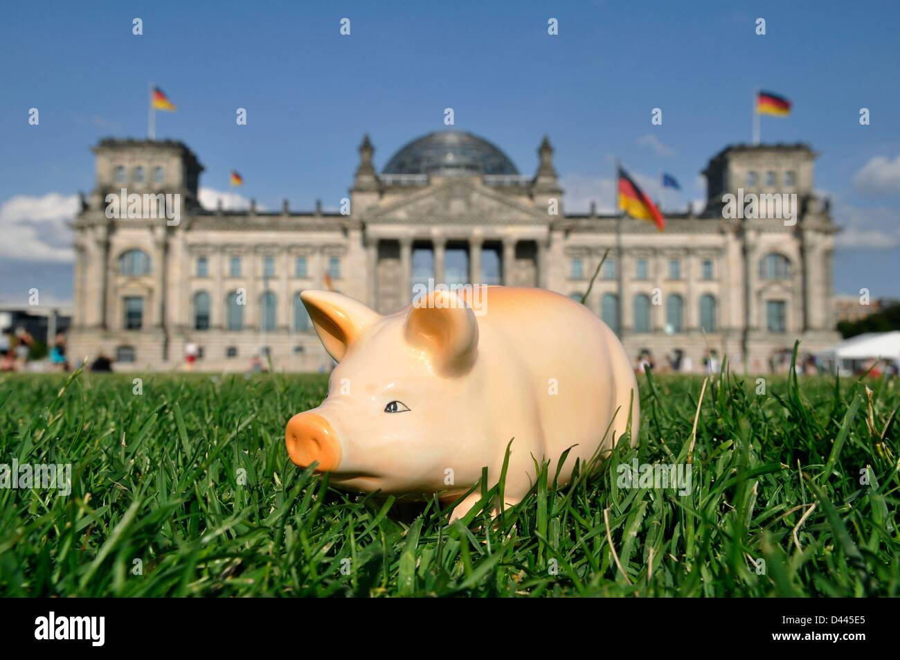 Illustration - A piggy bank is pictured standing on the lawn in front of the German Reichstag in Berlin, German, Stock Photo
