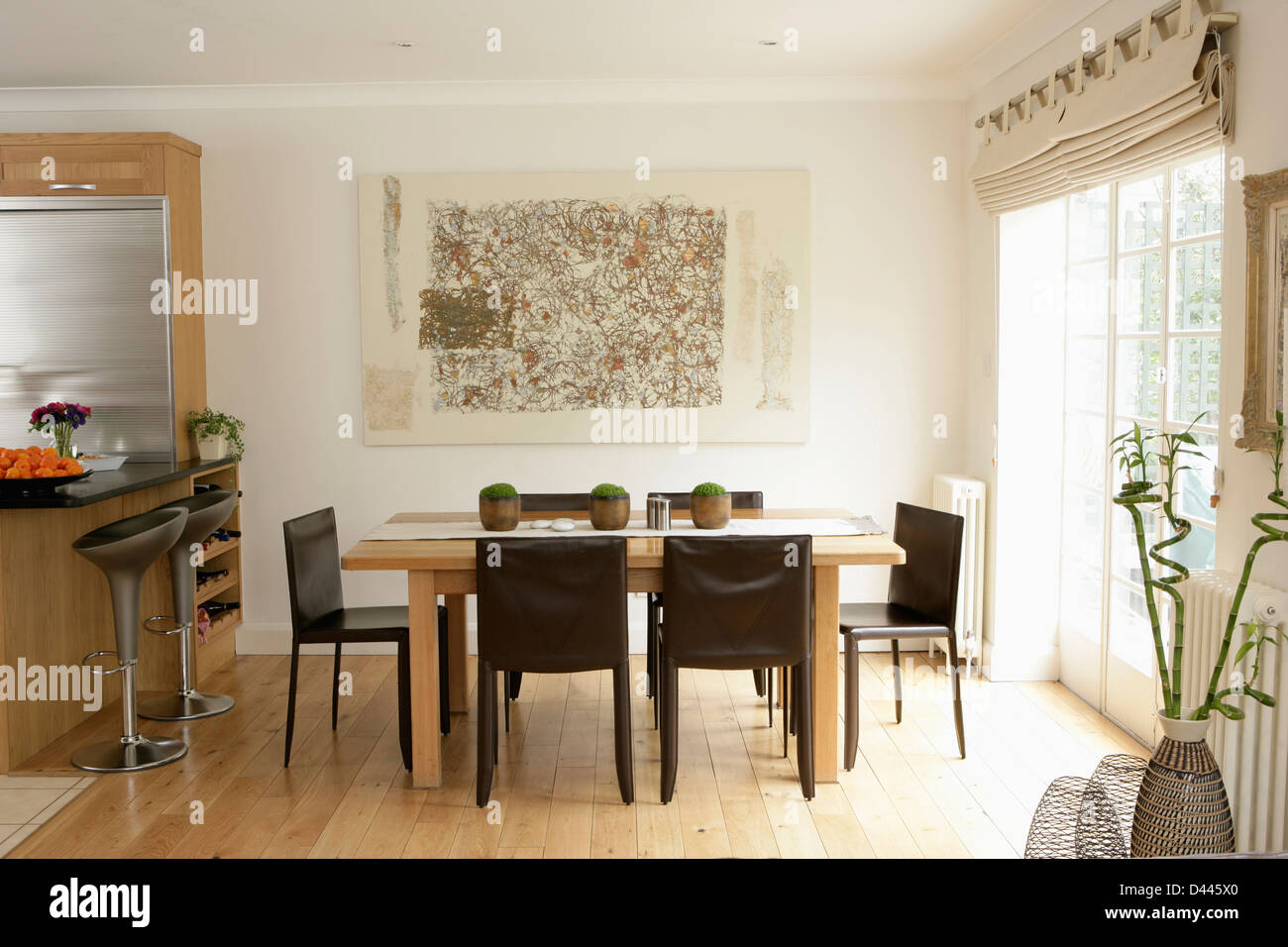 Black Chairs And Pale Wood Table In Dining Area Of Modern White Kitchen  With Wooden Flooring