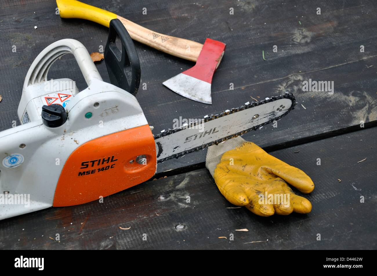 A chainsaw, work gloves and an axe are pictured on a table in Berlin, Germany, 20 November 2011. Photo: Berliner Stock Photo