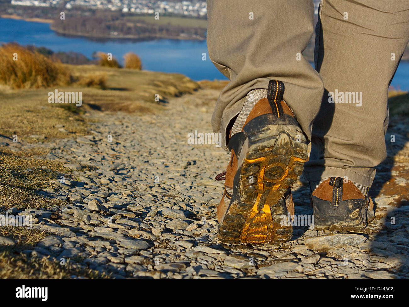 Walker on day trek in the Lake District with close up on outdoor footwear and the background scenery - Stock Image