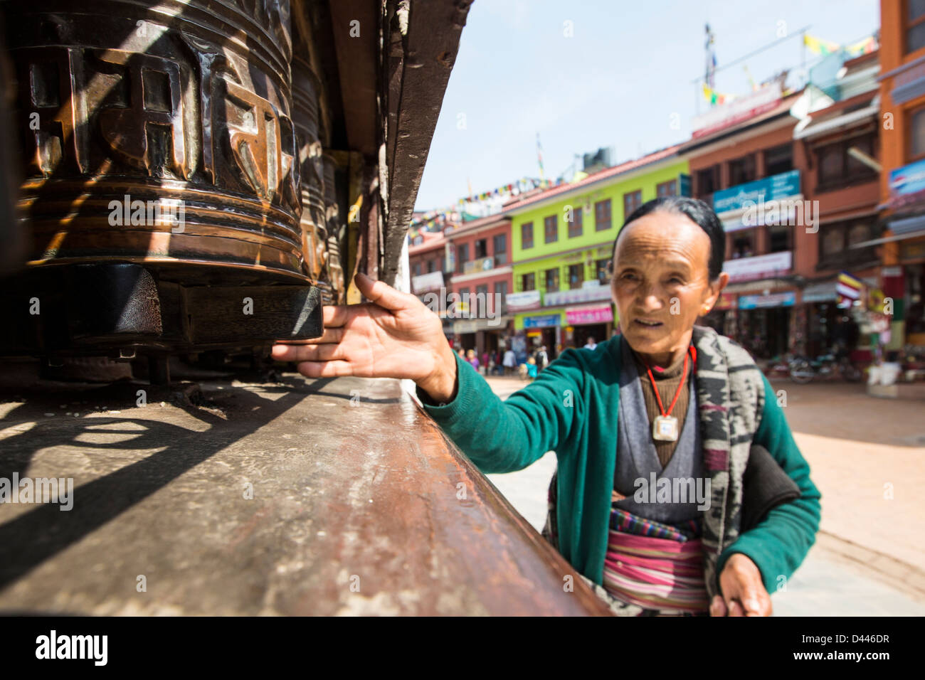 Woman spinning prayer wheels at Boudhanath Stupa, Kathmandu, Nepal - Stock Image