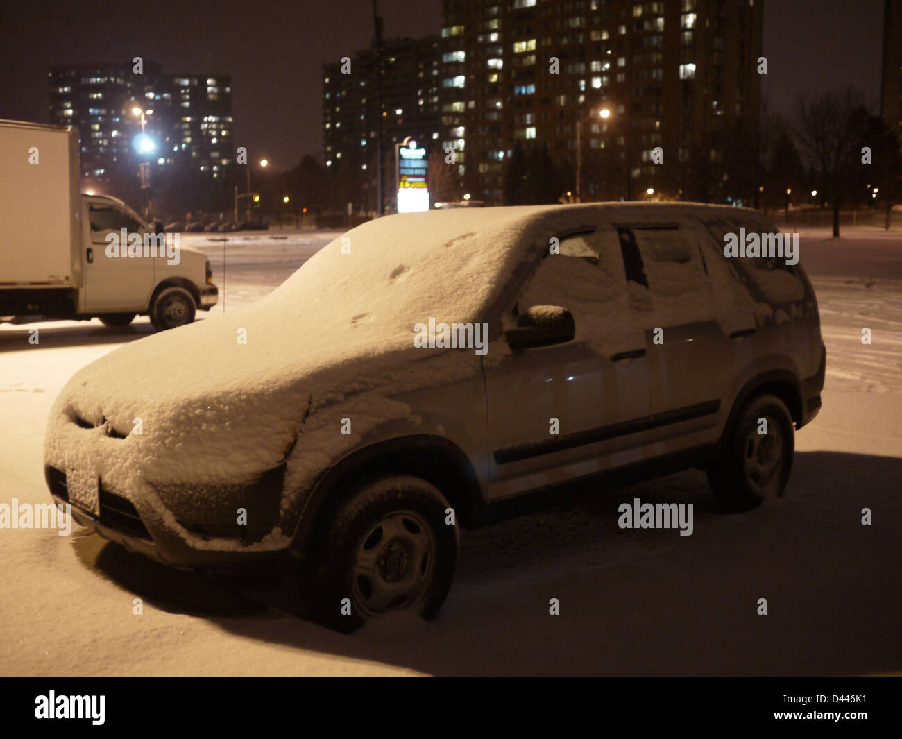 snow covered car parking lot night - Stock Image