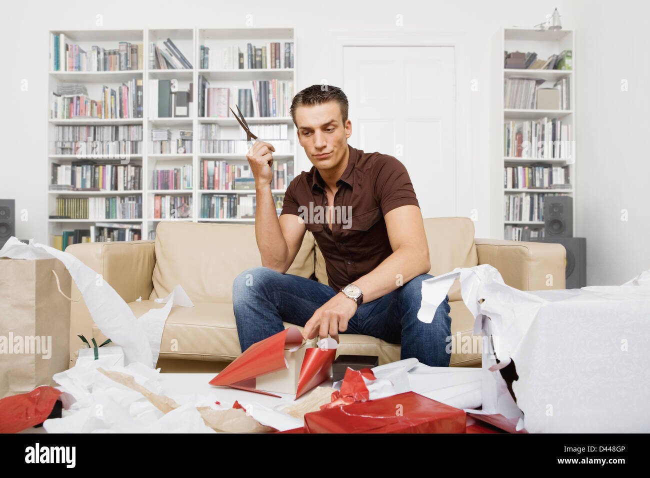 hunky dude doesn't know how to wrap presents - Stock Image