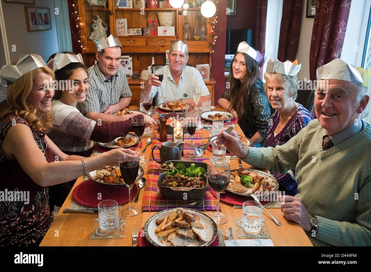 Horizontal portrait of three generations of a family enjoying Christmas lunch together round the table. Stock Photo