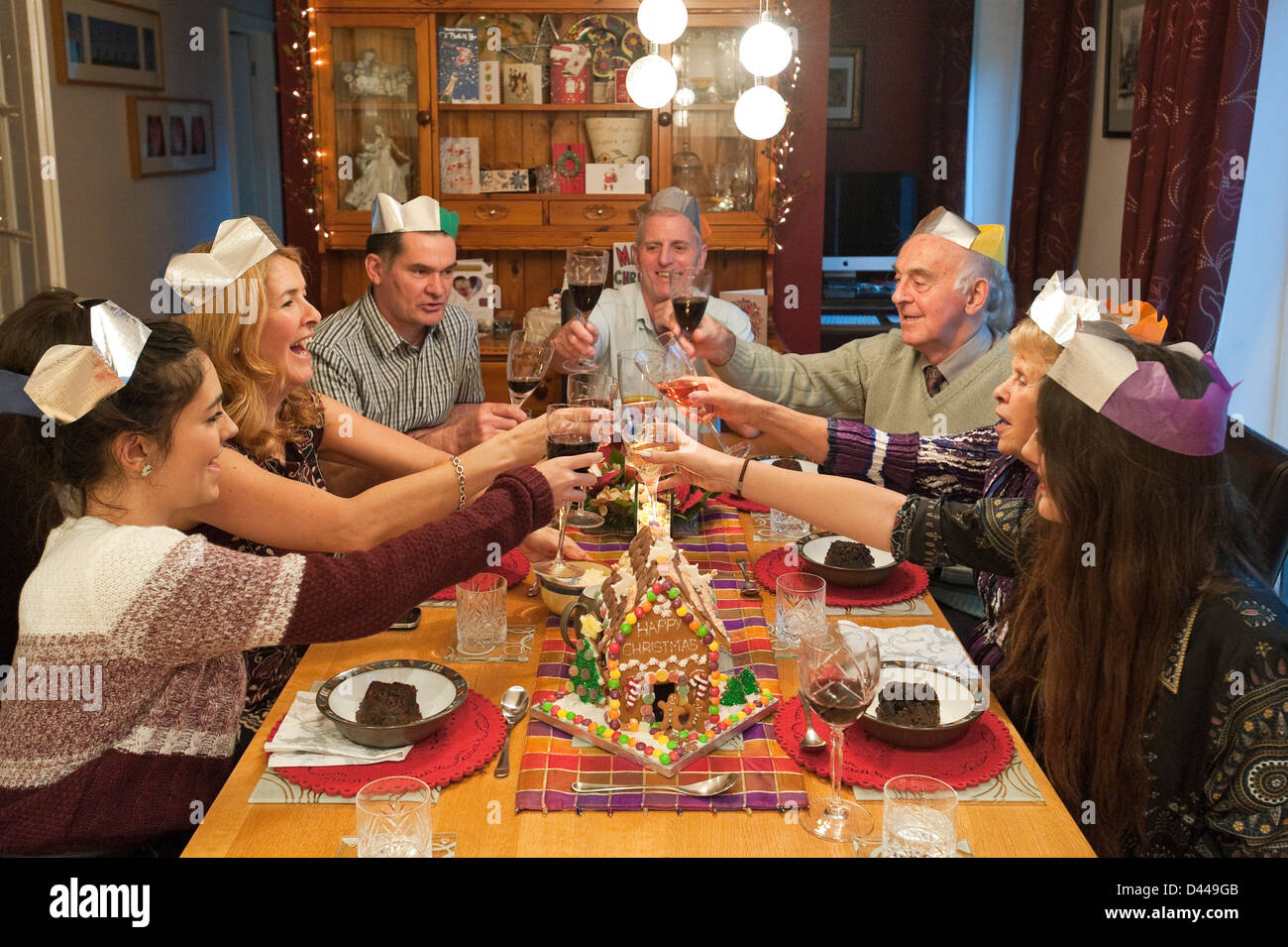 Horizontal portrait of three generations of a family enjoying Christmas lunch together round the table. - Stock Image