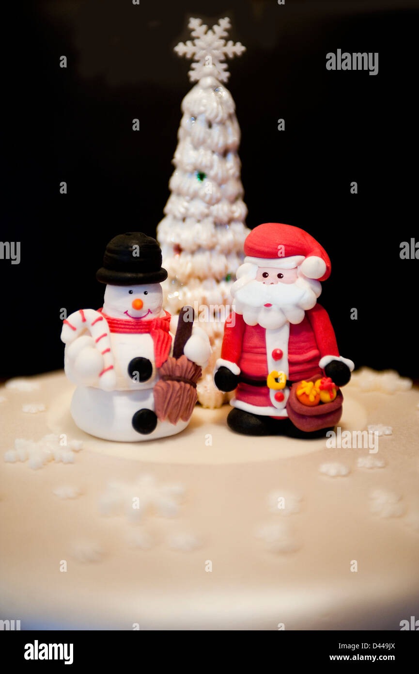 Vertical close up of fun modeled figures of Father Christmas and a snowman standing on a Christmas cake. - Stock Image