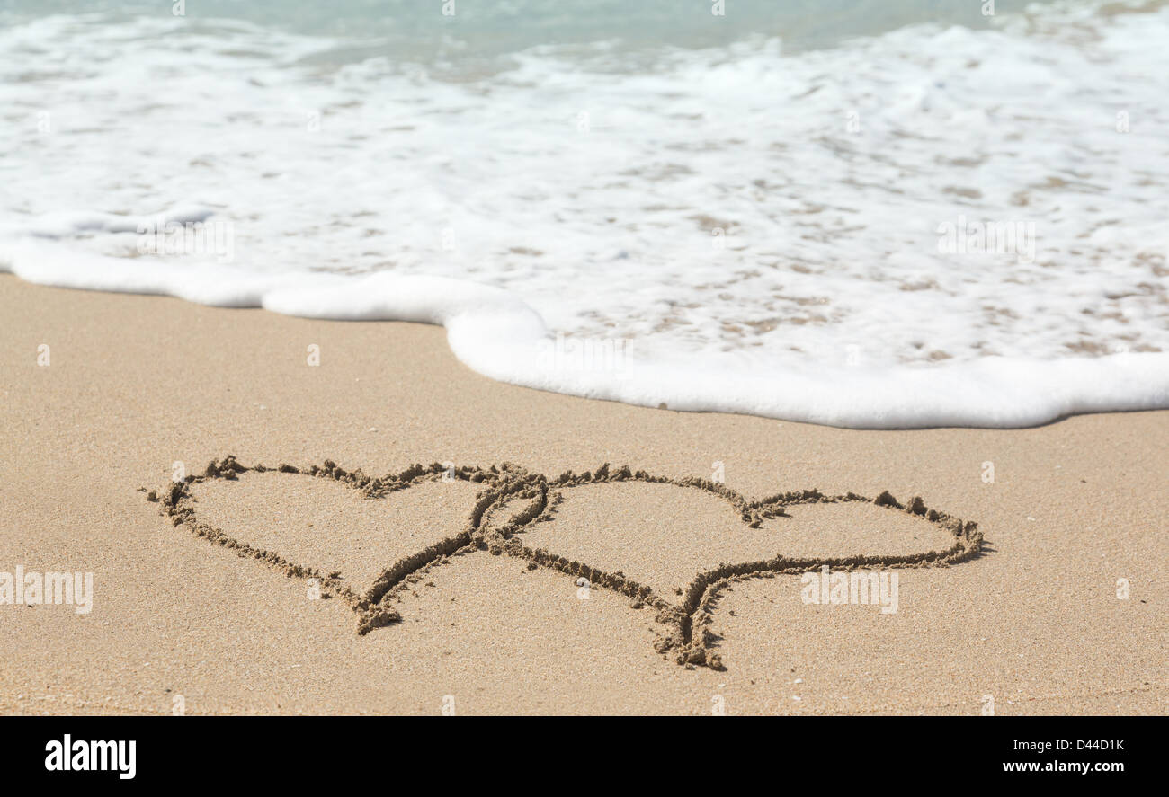 Linked love hearts drawn in the sand on a tropical beach by ocean surf - love holiday vacation romance concept - Stock Image
