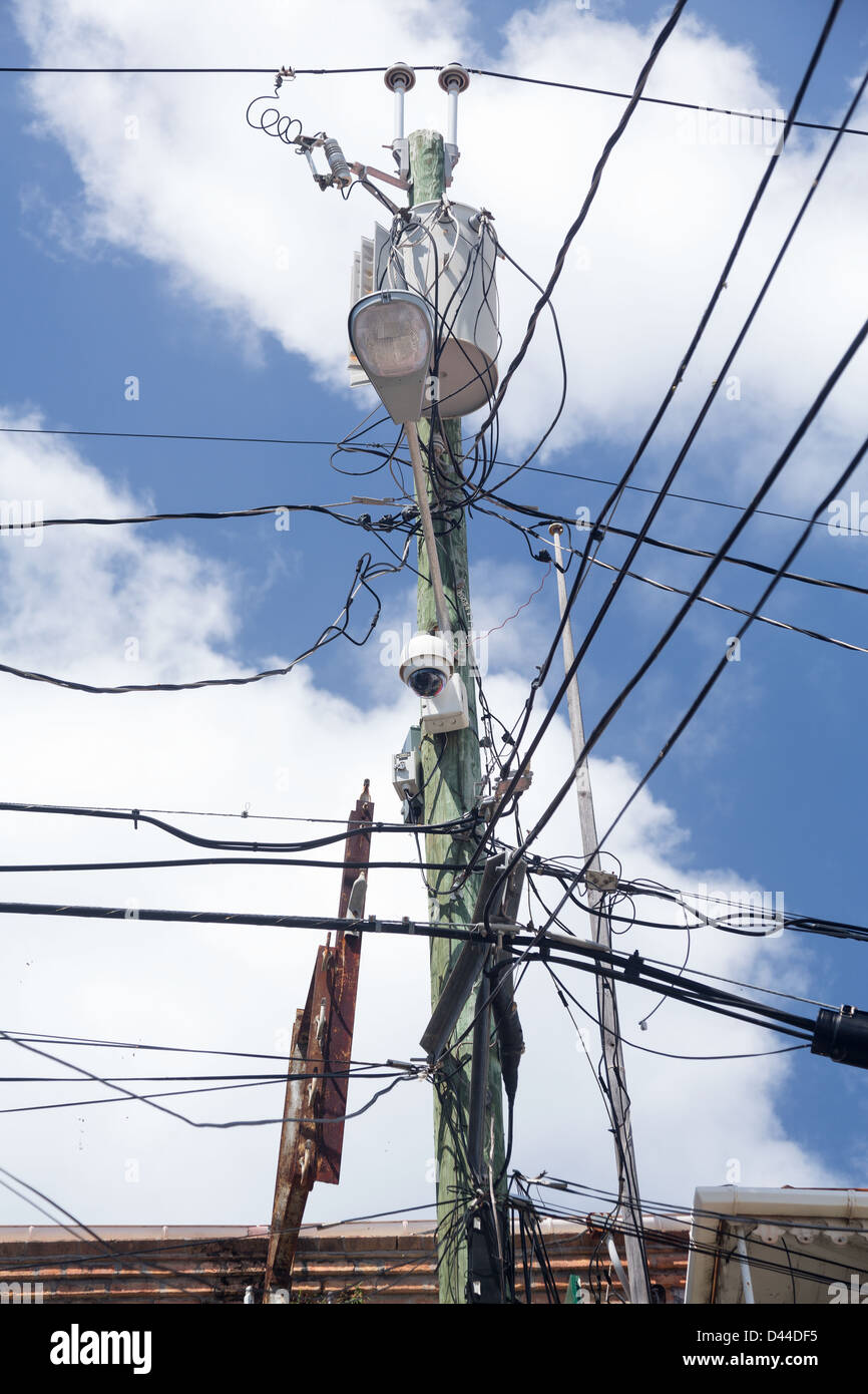 Complicated wiring forms tangled mess on power pole with light and camera - Stock Image