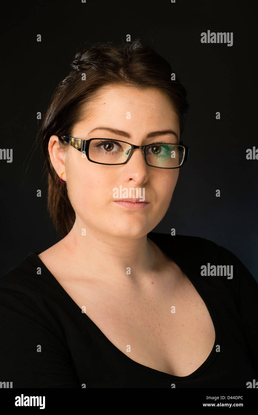 A young woman, brown hair and eyes, wearing glasses spectacles  UK - Stock Image