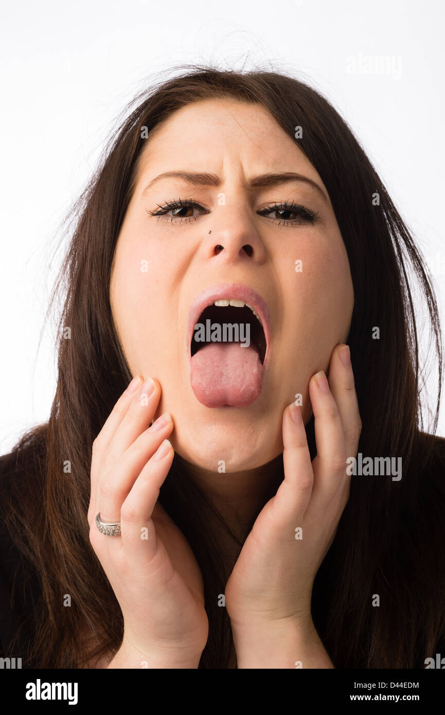 A young ill sick ailing woman, brown hair, sticking out her tongue UK - Stock Image