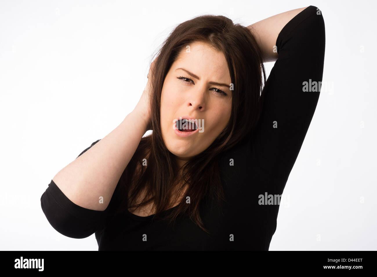 A young tired sleepy yawning woman, brown hair, UK Stock Photo