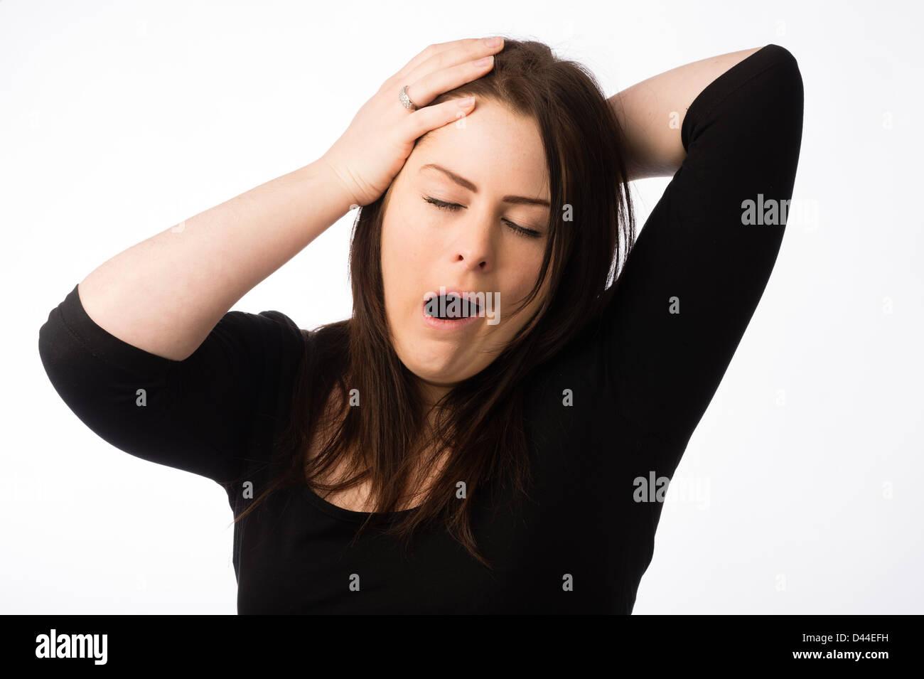 A young tired sleepy yawning woman, brown hair, UK - Stock Image