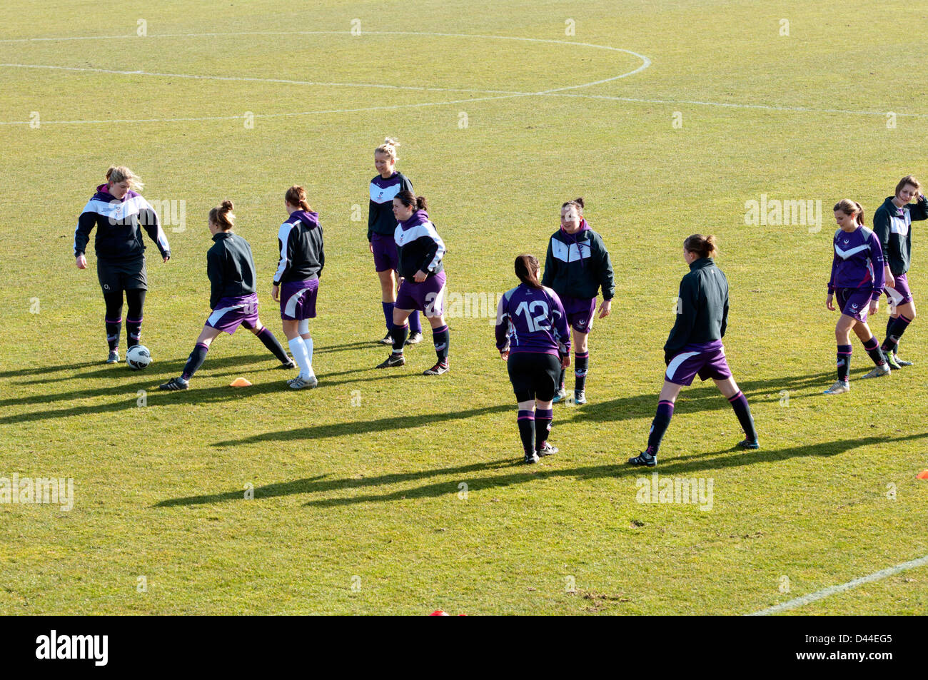 University sport, women`s footballers doing warm-up exercises before match - Stock Image