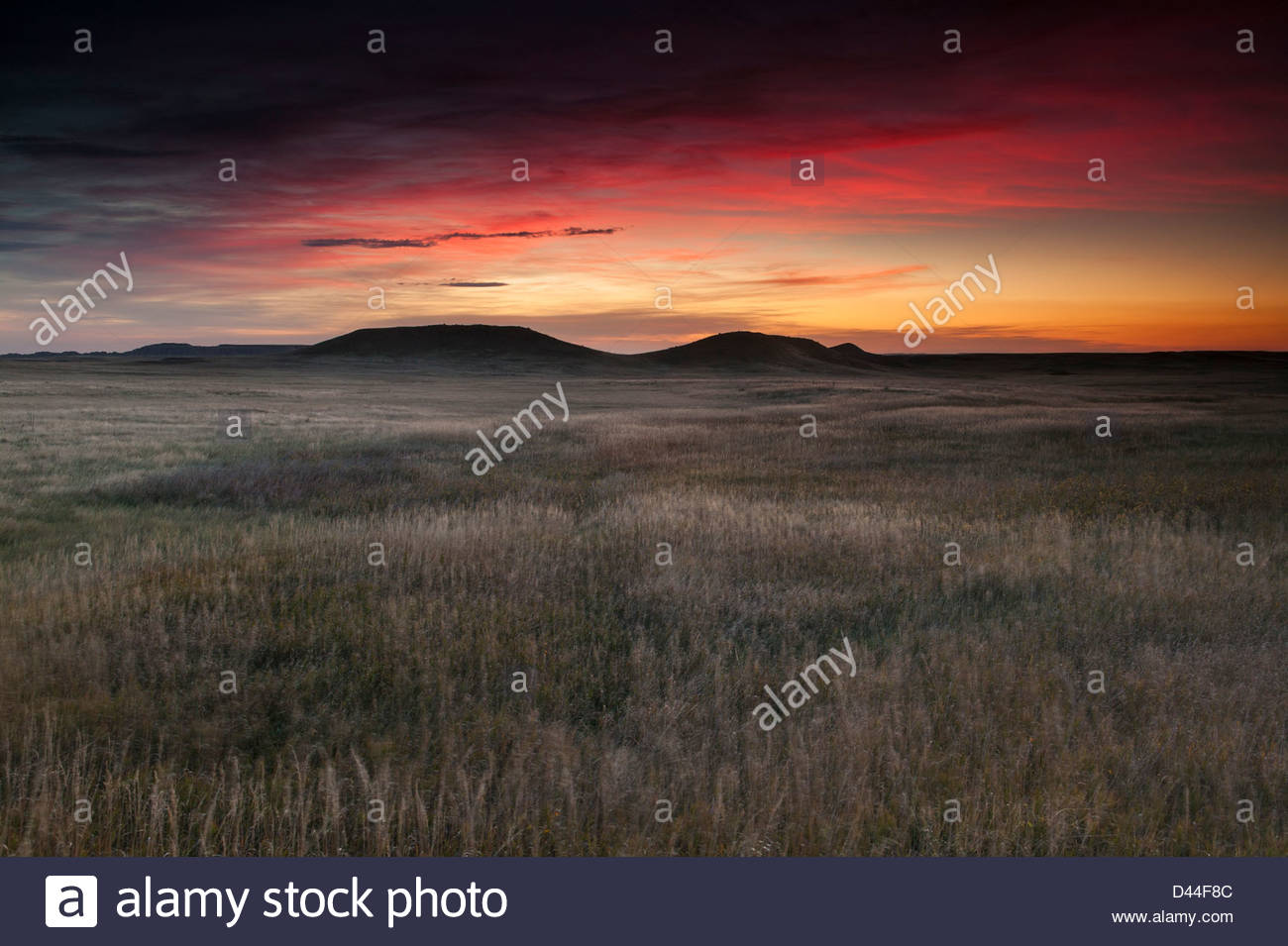 A colorful sunrise lights up the sky above a grass prairie near Dillon Pass in Badlands National Park, South Dakota. - Stock Image
