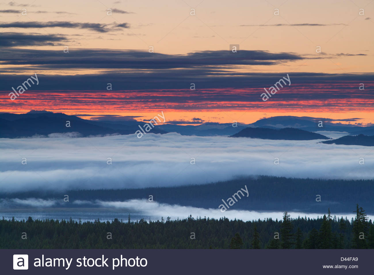 Fog rises from the Pend Oreille River as the sunrise reddens the clouds above mountains near Newport in Washington - Stock Image