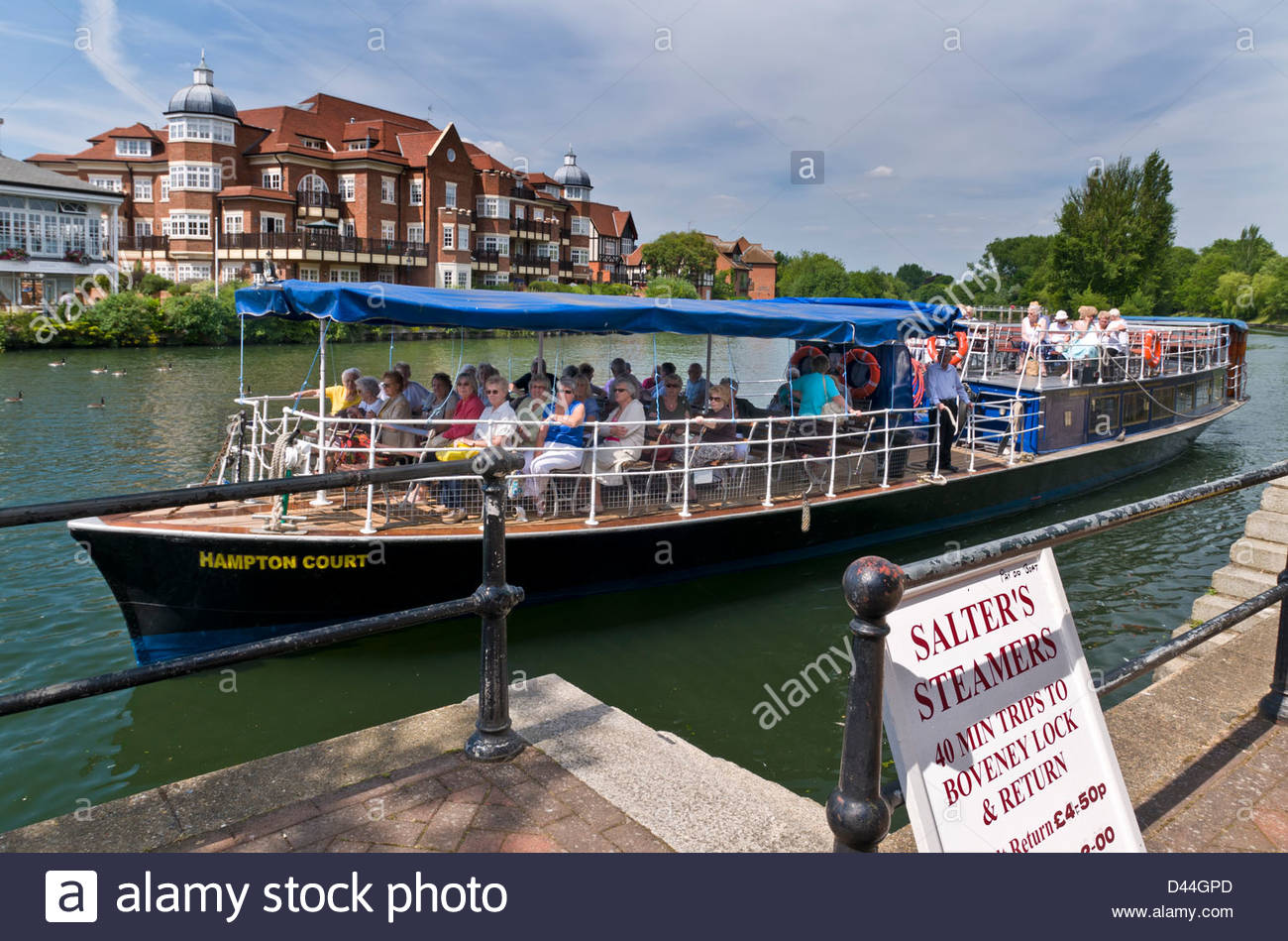 River Thames cruise boat and passengers leaving the mooring at Windsor Berkshire with village of Eaton behind Berkshire - Stock Image