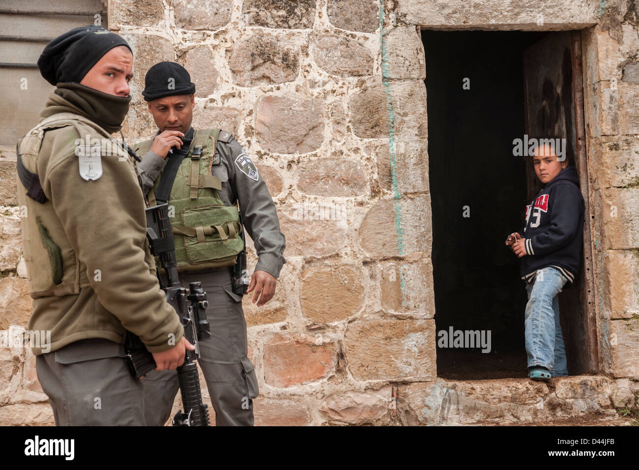 Hebron, West Bank, Israel. A Palestinian girl looks at two Israeli Border Guards. - Stock Image