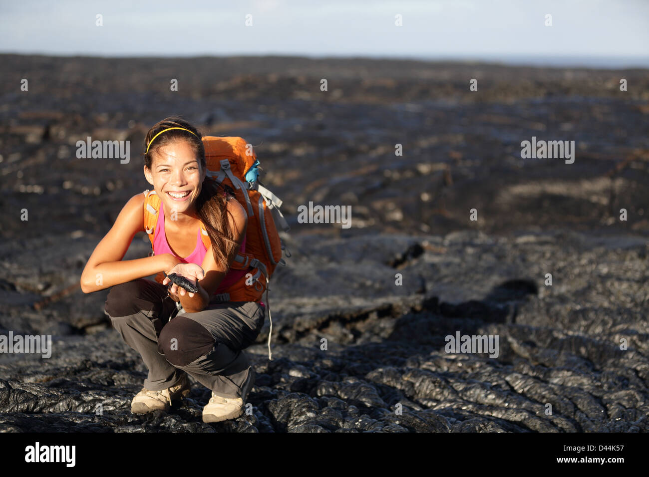 Portrait of young woman showing fresh cooled lava from Kilauea volcano around Hawaii volcanoes national park - Stock Image