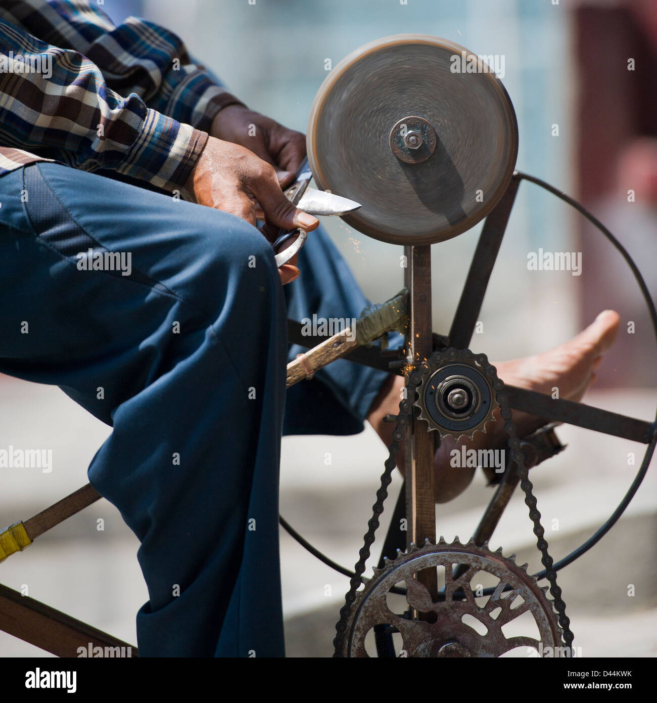 Man sharpening knives and scissors on the street in Nepal - Stock Image