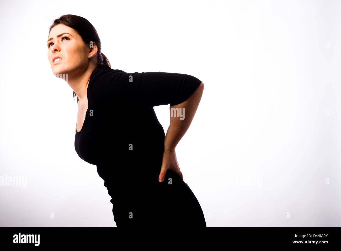 A young woman, brown hair, suffering back pain, UK - Stock Image