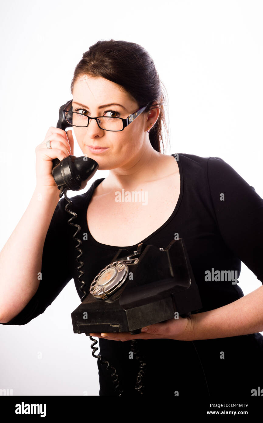 A young woman, brown hair holding using an old fashioned telephone, UK - Stock Image