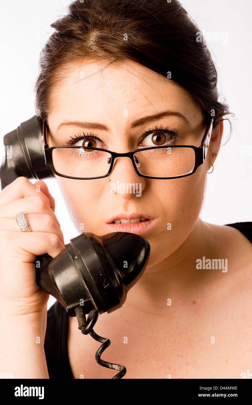 A young woman, brown hair looking shocked, holding an old fashioned telephone, UK - Stock Image