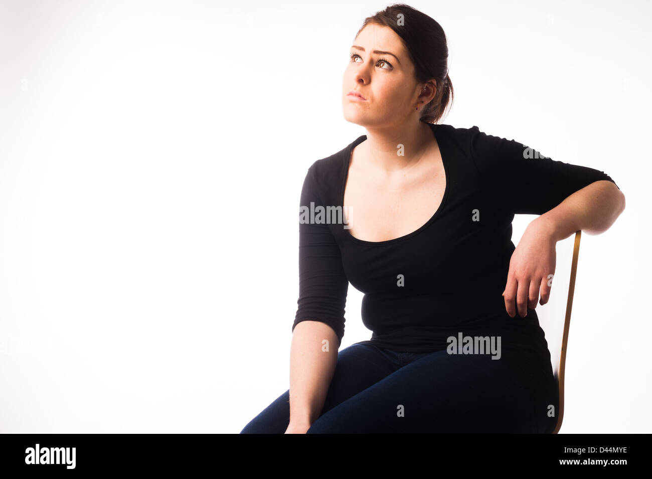 A young woman, brown hair, sitting alone, looking sad down depressed lonely UK - Stock Image