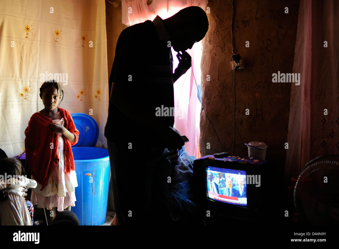 NIGER Niamey, malian refugees watching TV with news with François Hollande and the war in Mali - Stock Image